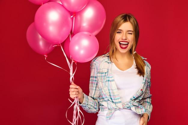 Модель женщины с розовыми воздушными шарами. подмигивать