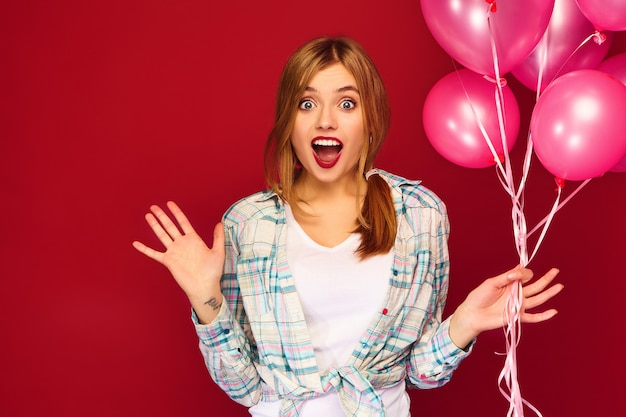 Взволнованная молодая женщина позирует с розовыми воздушными шарами