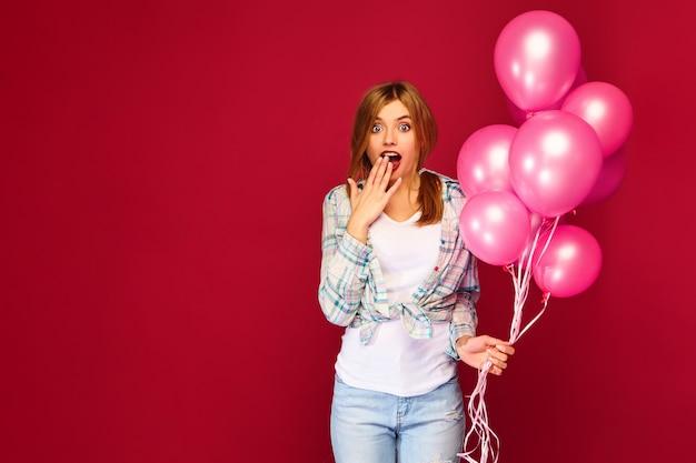 興奮した若い女性がピンクの気球でポーズ