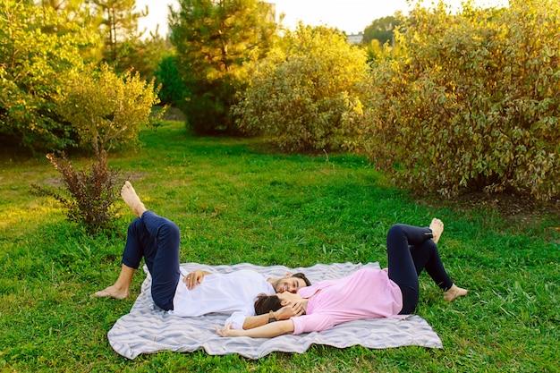 若いカップルは草の上に横たわると笑みを浮かべて、お互いに優しく触れます