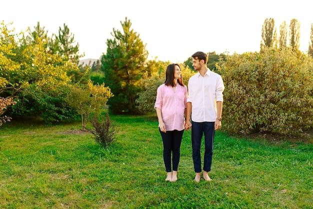 Портрет веселая беременная пара смотрит друг на друга в парке