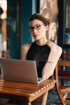 カフェの仕事のテーブルに座って、メガネで洗練されたビジネス女性