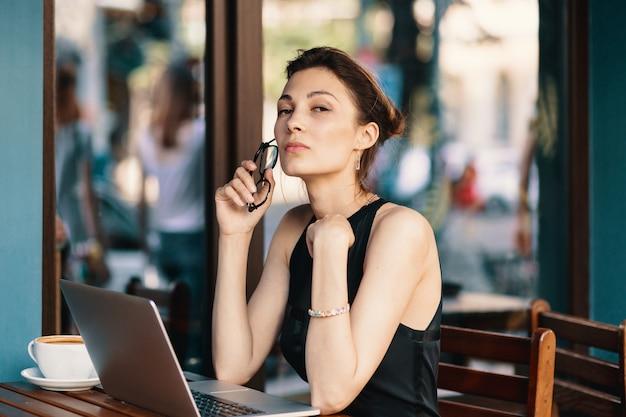 Изысканная деловая женщина в очках, сидя за столом в кафе, работает на ноутбуке