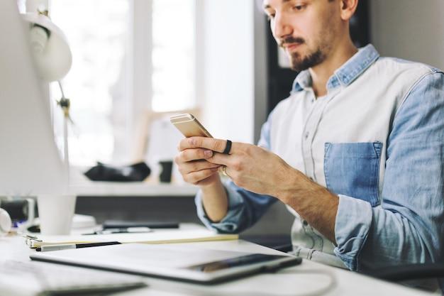 携帯電話を使用してオフィスで働くハンサムな実業家