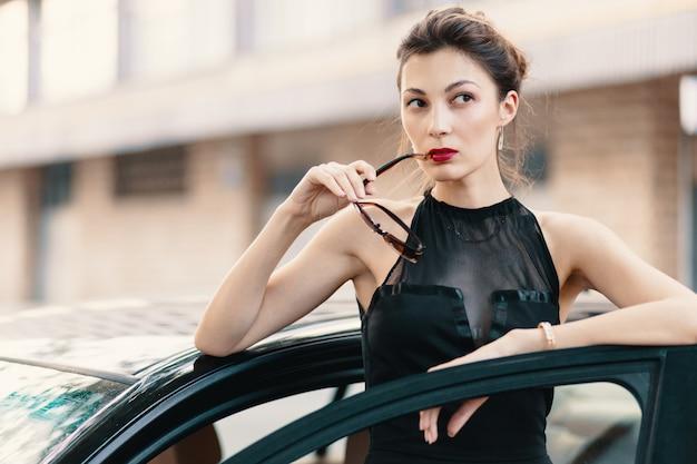 Она готова покорить мир - уверенная в себе женщина, стоящая в дор машине