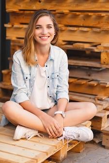 かなり笑顔の女の子、ジーンズ、ショートパンツ、シャツのポーズを着て
