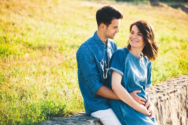 妊娠中の妻を抱いて若い白人男
