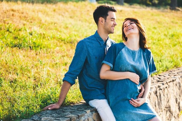 Молодой человек кавказской обнимает беременную жену