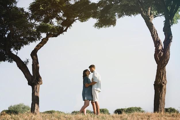 Счастливая и молодая беременная пара обниматься на природе
