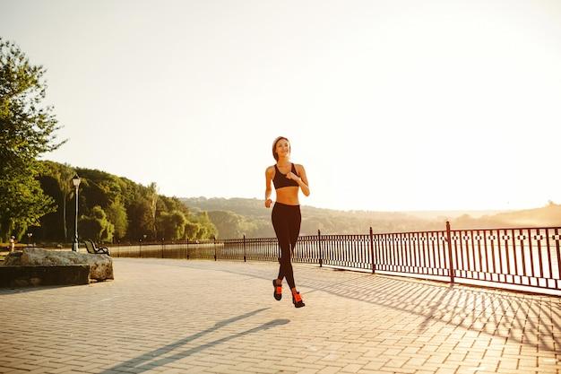 走っている女性。日当たりの良い明るい光の中でジョギングランナー。公園の外の女性フィットネスモデルトレーニング