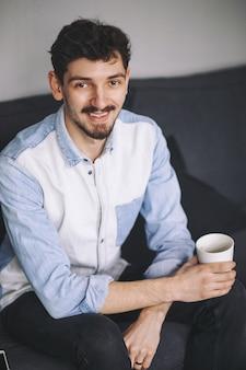 コーヒーを飲んでいるソファに座っているハンサムなカジュアルな男