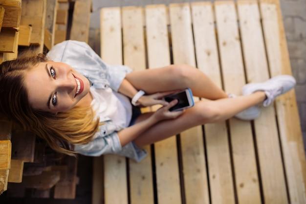 スマートフォンを使用してパレットに座っている魅力的な女の子