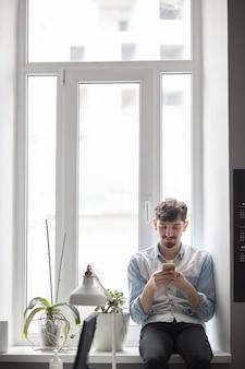 手で電話で窓に座っている若いスタイリッシュな男