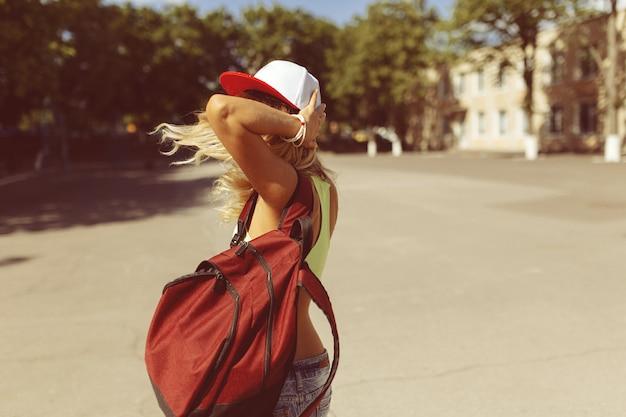 通りを歩いてセクシーな金髪の若い女性