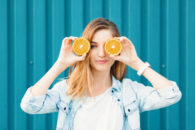 Беззаботная молодая красивая девушка, использующая две половинки вместо апельсинов