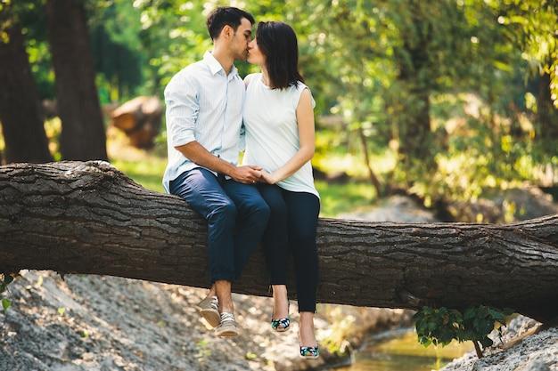 Красивая беременная пара расслабляющий снаружи в лесу