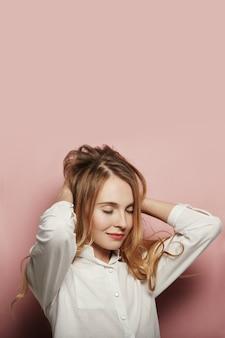 Милая молодая женщина представляя на розовой предпосылке
