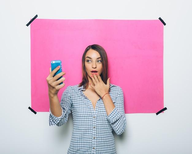 カメラ付き携帯電話で写真を撮るかなり若い女性