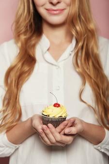おいしいおいしいカップケーキを保持している女性手