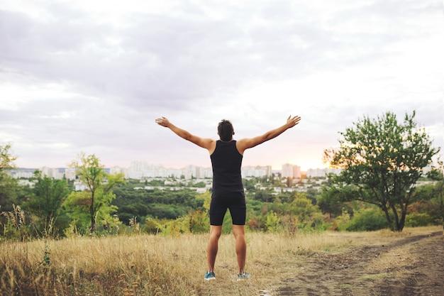 トレーニング後の夕焼け空に手を上げる若い男