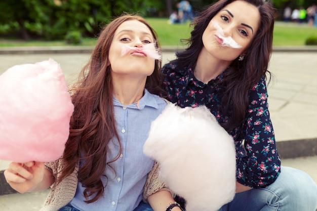 Две веселые девушки веселятся с сладкой ватой на улице