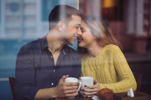 コーヒーショップでコーヒーを飲むことを愛するカップル