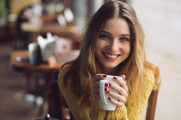 Очаровательная девушка пьет капучино