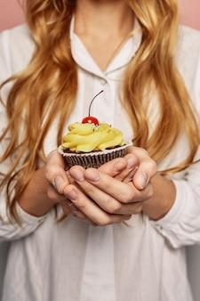 白いシャツで魅力的な女の子がカップケーキを保持しています。