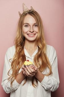 Улыбающаяся женщина, с короной, держит на день рождения кекс