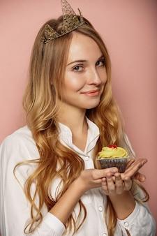 クラウンとカップケーキの魅力的な女の子