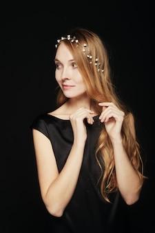 黒の背景に美しい若い女性の肖像画