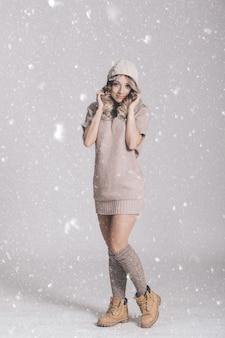 雪の背景にニットの服の若い魅力的な女性の美しい肖像画