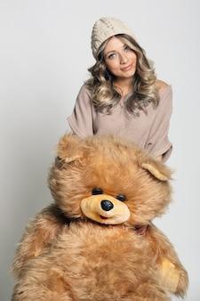 Повседневная улыбающаяся молодая женщина в вязаной одежде держит большого мягкого плюшевого мишку