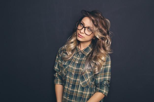 トレンディなメガネとカジュアルな服を着て、黒の背景にポーズをとって若い美しいブロンドの髪の肖像画