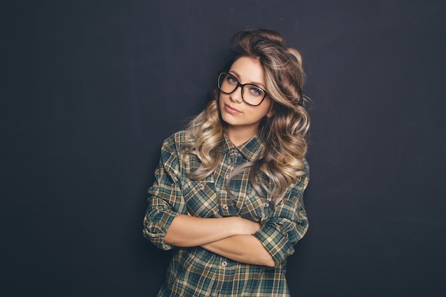 Портрет молодой красивой светловолосой носить модные очки и повседневную одежду и позирует на черном фоне