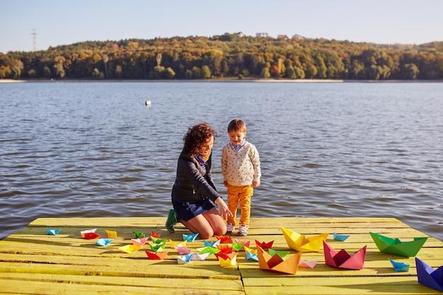 Мама и сын играют с бумажными корабликами у озера