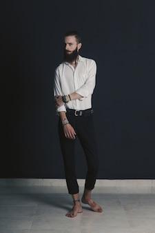 黒の背景上のスタジオで流行に敏感なスタイルのひげを生やした男白いシャツ