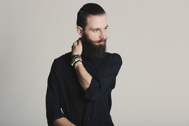 白い背景の上のスタジオで流行に敏感なスタイルのひげを生やした男黒シャツ