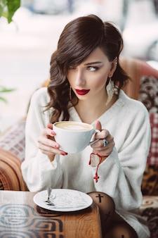 トレンディなカフェでコーヒーを飲む若い女の子