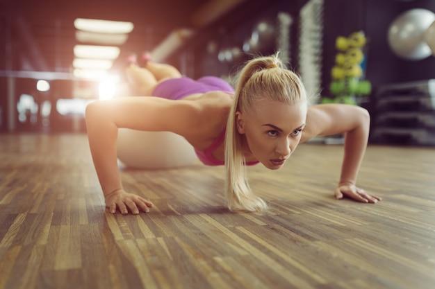 強くて美しい運動女性のジムでトレーニング