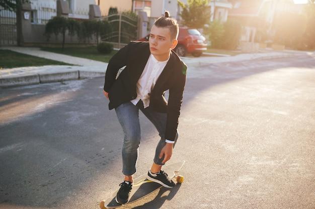 道路に行くロングボードを持つ男の画像