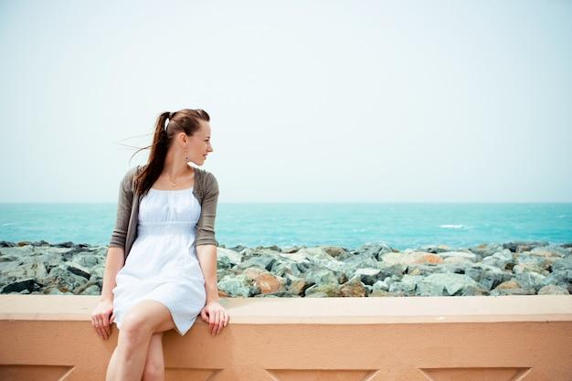 Молодая красивая женщина позирует на пляже