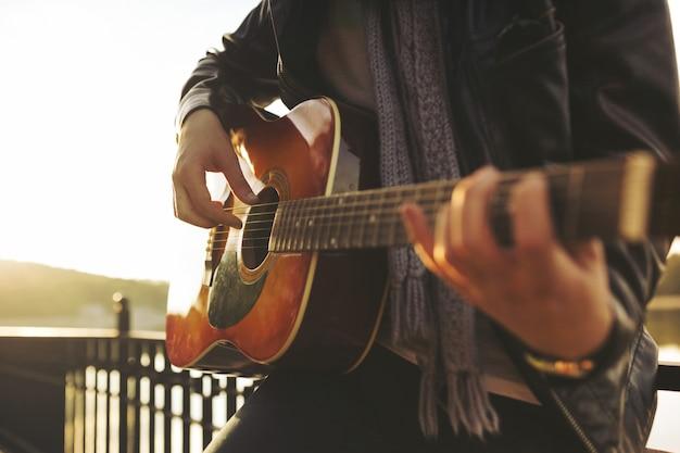 Молодой человек играет на гитаре на озере