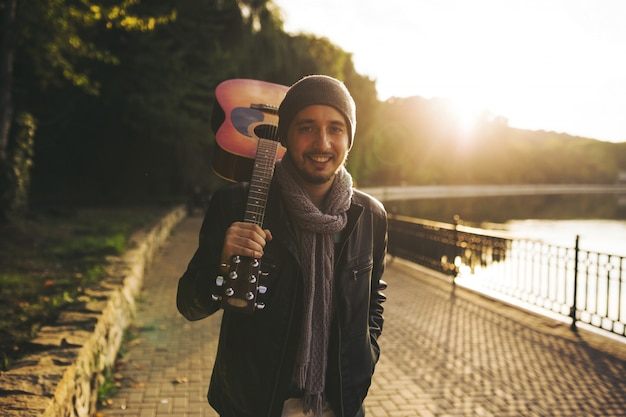 若い男は湖とギターを持って歩く