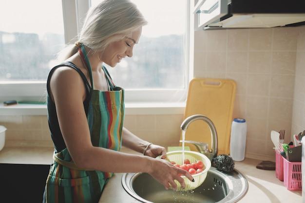 水の流れの下でキッチンで新鮮な野菜のトマトを洗う女