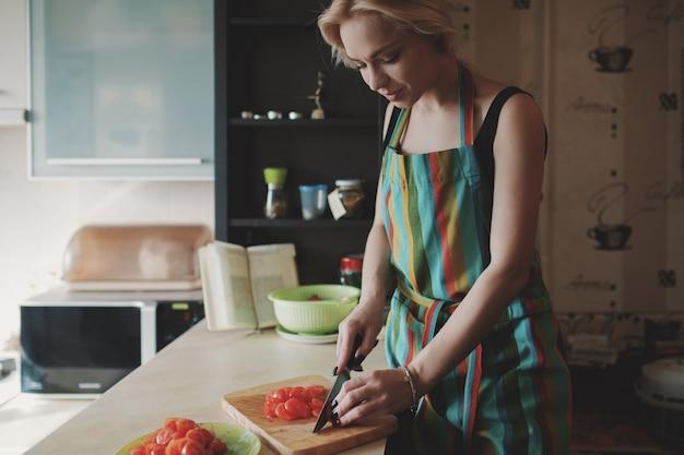 若い女性がトマトをスライス
