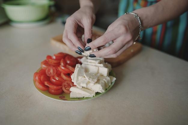 Женщина режет сыр