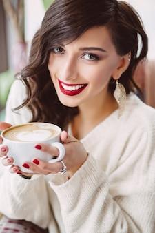 Молодая девушка пьет кофе в модном кафе