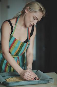 キッチンでピザを調理する女性
