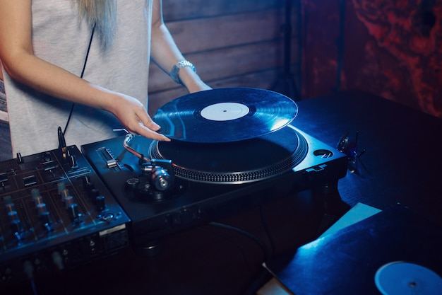 Милая диджей женщина с удовольствием играет музыку на вечеринке в клубе